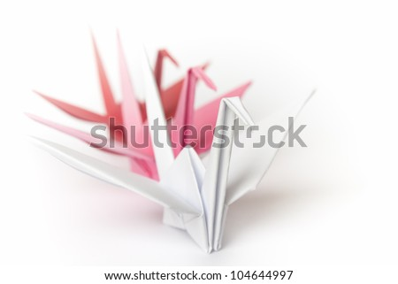 3 paper birds lining up on a white background. Shallow depth of field. - stock photo