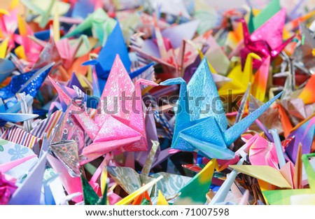2 paper birds on top of a pile of smaller paper birds. Shallow depth of field. - stock photo