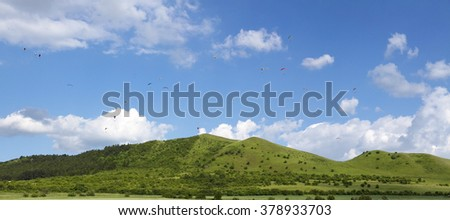 22 paragliders flying over hill - stock photo