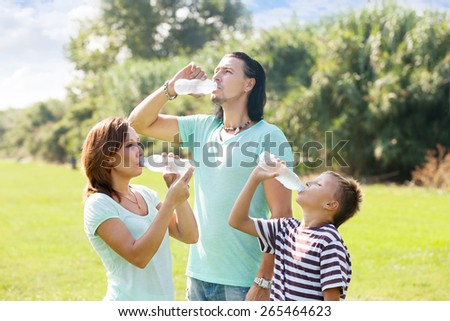 parents with teenager son drinking water from plastic bottles in summer park - stock photo
