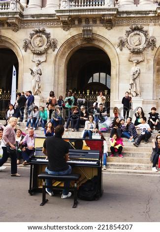 Paris, France -September 21,2014: Unidentified pianist play before public outdoors . Paris Opera - stock photo