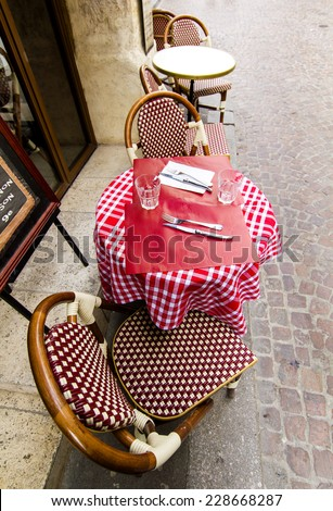 Paris - traditional french cafe with it's round tables with Parisian cafe table with checked napkinand chairs outdoors on the sidewalk, wide-angle lens - stock photo