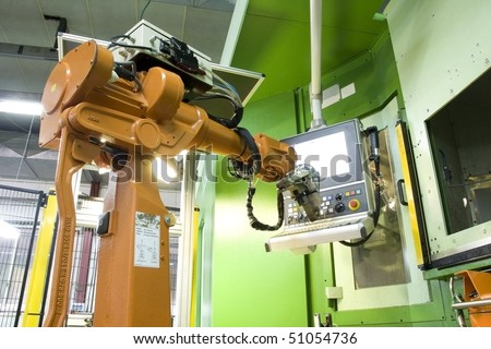 part of the cnc milling machine with control panel and robot - stock photo