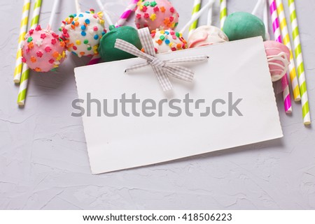 Party background. Colorful  bright cake pops, paper straws  and empty tag on  grey textured  background. Selective focus. Place for text. - stock photo