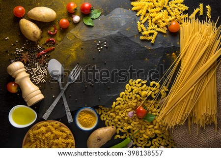 pasta tagliatelle with tomatoes, vegetables and spices for tomato sauce on dark  background, top view - stock photo