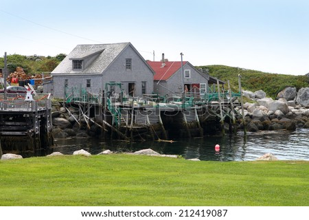 Peggy's Cove, Nova Scotia, August 6, 2014,: Bagpiper playing music in front of the lighthouse in touristic Peggy's Cove, Nova Scotia, Canada  - stock photo