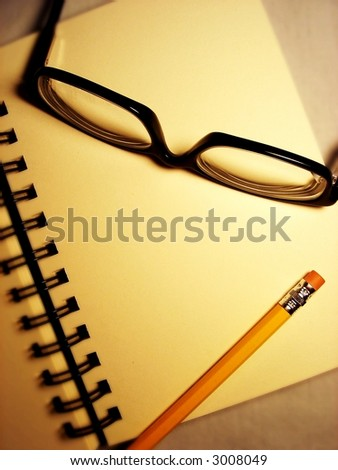 pencil and glasses on sketch book - stock photo