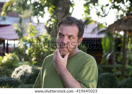 Pensive mature man in the yard of his house - stock photo