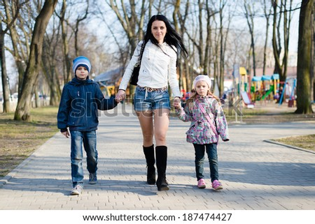 3 people beautiful mom walking in the park with her son and daughter happy smiling & looking at camera on spring or autumn outdoors background   - stock photo