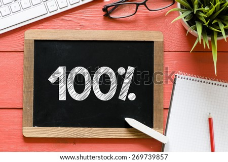 100 percent Handwritten on blackboard. 100 percent Handwritten with chalk on blackboard, keyboard,notebook,glasses and green plant on wooden background - stock photo