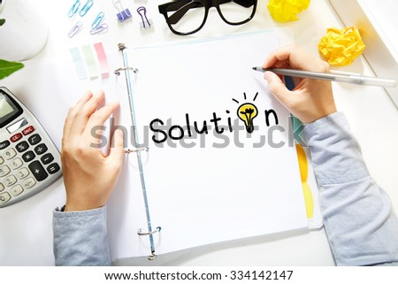 Person drawing Solution concept on white paper in the office - stock photo