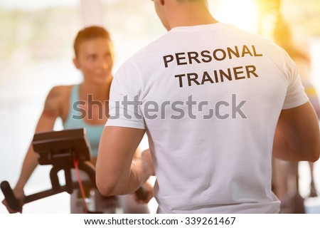 Personal trainer on weights lifting training with  client - stock photo