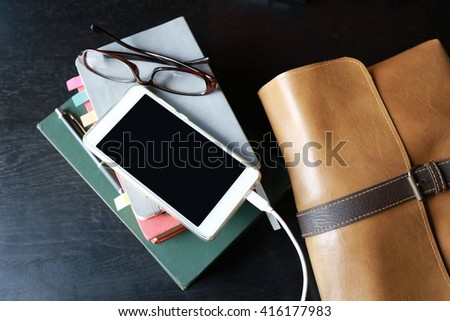 phone eyeglasses book and leather bag background - stock photo