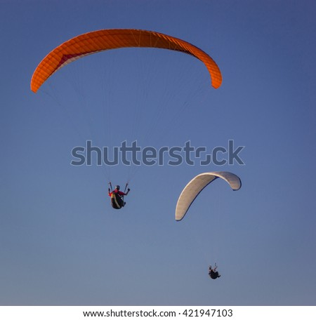 Photo by air. Red and white paragliders flying against the background of blue sky  - stock photo