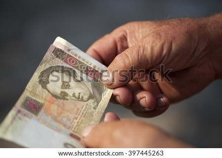 photographed close-up of one hundred Ukrainian hryvnia in the hands of the old man, small depth of field - stock photo