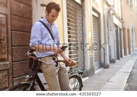 Picture of a young business man who stopped on his bike to look at something on his smartphone - stock photo