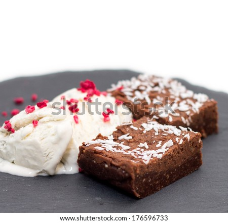 2 pieces of fresh homemade brownies with licorice vanilla ice-cream and dehydrated raspberries on rough-looking grey slate plate isolated on white - stock photo