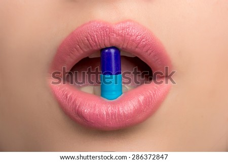 Pill between lips.  Close up young woman with medicine pill in her sensual  mouth vertical - stock photo