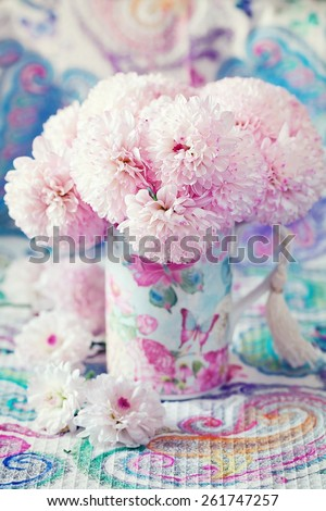 pink flowers in a beautiful mug on a beautiful tablecloth. - stock photo