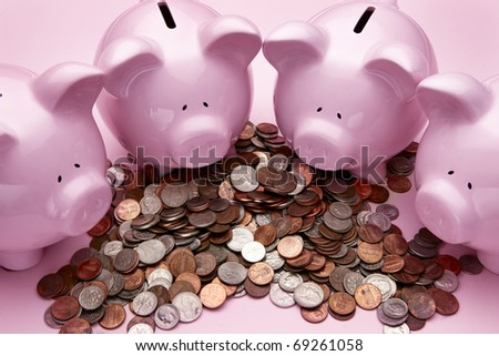 4 pink piggy banks feasting on a pile of coins - stock photo
