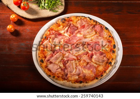 Pizza with bacon, ham and cheese - stock photo