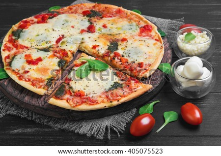 Pizza with mozzarella into balls and shredded cheese, cherry tomatoes,  cut off slice, lettuce on a cutting board round served on a dark black background wooden surface - stock photo