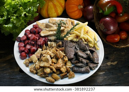 Plate of snacks, meat, potatoes, sausage, cracklings - stock photo