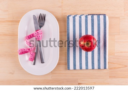 plate with red apple and measure tape in diet concept on wooden mat. Above view - stock photo