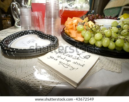 """Please shut up about your wedding"" napkins, heart shaped paper plates, and a fruit tray set on a table. - stock photo"