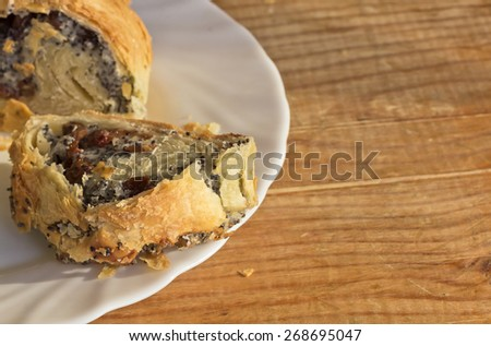 Poppy roll with raisins on wooden table in white plate.Closeup. - stock photo