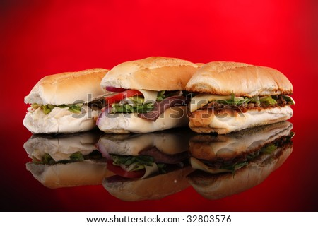 3 popular sandwiches - Chicken Caesar, Deli giant and Philly on red - stock photo