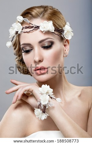 Portrait of a beautiful blonde woman in the image of the bride with flowers in her hair. Picture taken in the studio on a blue background - stock photo