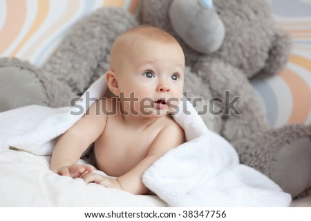 Portrait of a lovely baby covered with white towel - stock photo