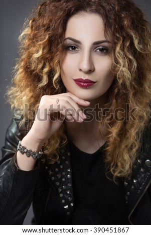 portrait of a red-haired woman with curly hair and an enigmatic smile in the style of glam rock - stock photo