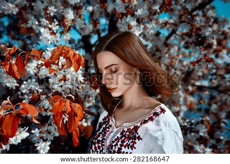 Portrait of a young woman standing near the tree with red leaves. - stock photo
