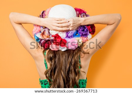 Portrait of attractive elegant woman in floral hat over bright background - stock photo