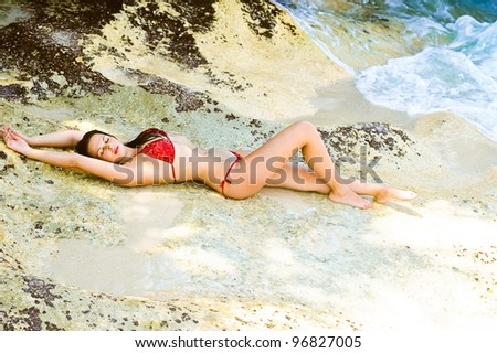 Portrait of attractive woman sleeping in bikini at beach - stock photo