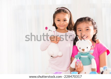 Portrait of cute little girls posing with their toys  - stock photo