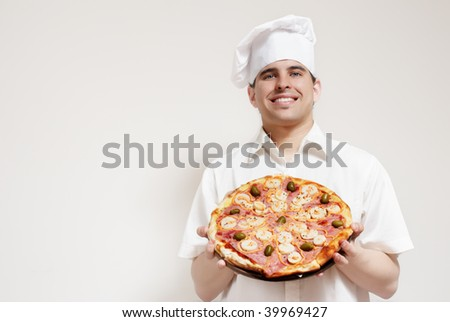 Portrait of happy attractive cook with a pizza in hands - stock photo