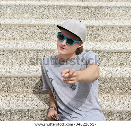 Portrait of  teenage boy pointing at the camera.Portrait of teenage boy talking at the camera . - stock photo