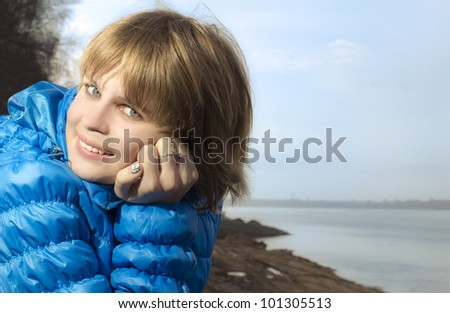 Portrait of the young blonde on river bank - stock photo