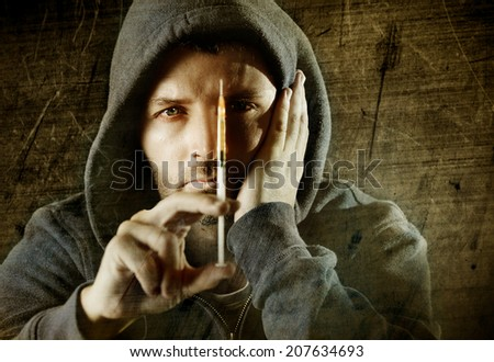 portrait of young sick drug addict man wearing hood holding heroin or cocaine syringe thinking and  looking wasted and depressed facing dope abuse and addiction on a grunge dirty texture background - stock photo