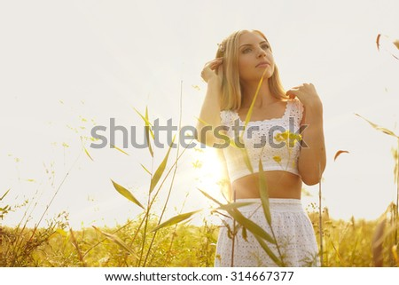 portrait of young woman in white dress outside in the meadow under sunlight - stock photo