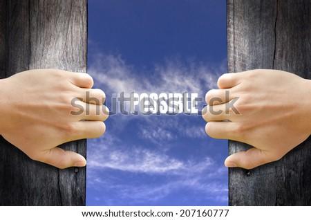 """Possible"" text in the sky behind 2 hands opening the wooden door. - stock photo"