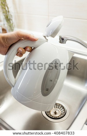 Pouring water into an electric kettle  - stock photo