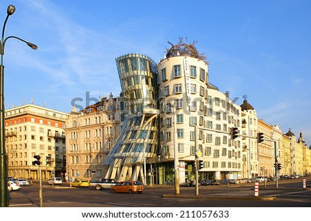 PRAGUE,CZECH REPUBLIC - JULY 18, 2014. Street view with famous  Dancing House ,its nickname is Fred and Ginger House after the famous dancers. Street traffic in Prague. - stock photo