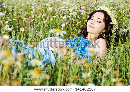 pregnant woman on the camomile field  - stock photo