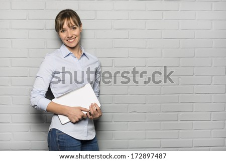 Pretty cheerful Woman holding a Tablet Pc, isolated over a gray brick wall - stock photo