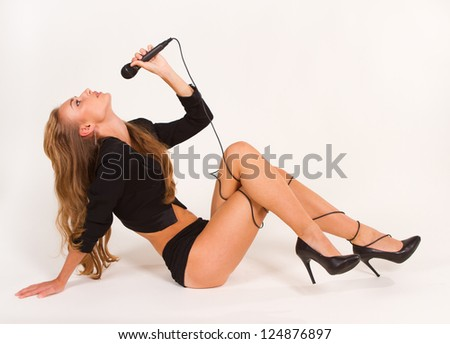 pretty girl with a microphone singing. Closeup on a white background. - stock photo