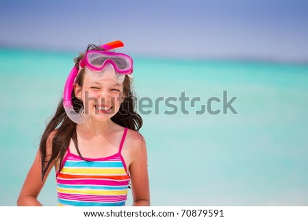 Pretty, smiling girl with swimwear and snorkel at a tropical beach. - stock photo